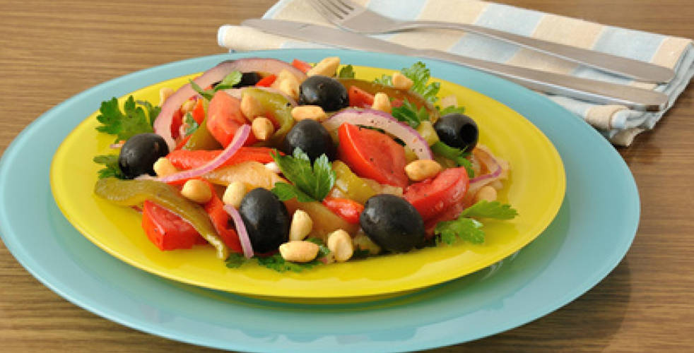 Fried pepper salad with tomatoes, peanuts and olives